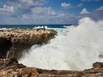 Волны бьются о скалистый берег